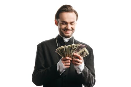 corrupt catholic priest smiling while holding dollar banknotes isolated on white Archivio Fotografico