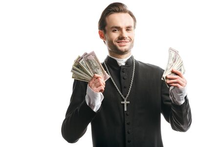 corrupt catholic priest smiling at camera while holding dollar banknotes isolated on white