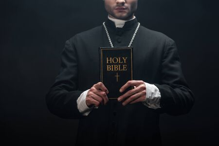 cropped view of catholic priest holding holy bible isolated on black