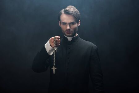 confident catholic priest holding necklace with cross while looking at camera on black background with smoke