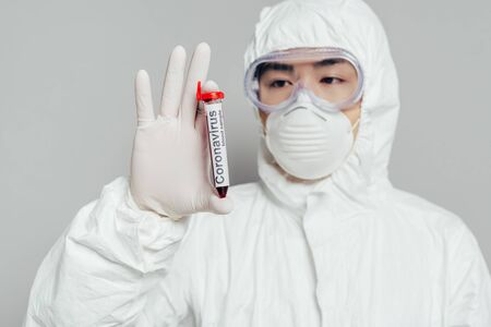 asian epidemiologist in hazmat suit and respirator mask showing test tube with blood sample on grey background