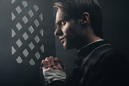 young thoughtful catholic priest praying with closed eyes in dark near confessional grille with rays of light Stock Photo
