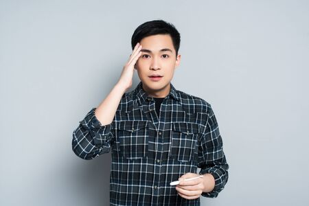 shocked asian man touching forehead and looking at camera while holding thermometer on grey background