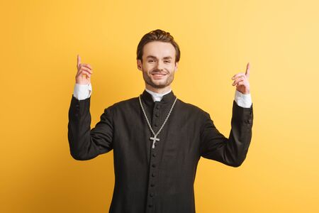 smiling catholic priest pointing up with fingers while looking at camera isolated on yellow
