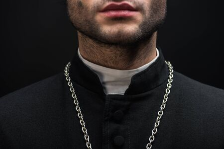 cropped view of catholic priest in black cassock with silver necklace isolated on black