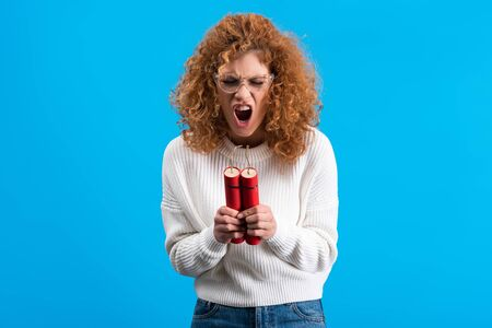 angry yelling woman in eyeglasses holding dynamite, isolated on blue