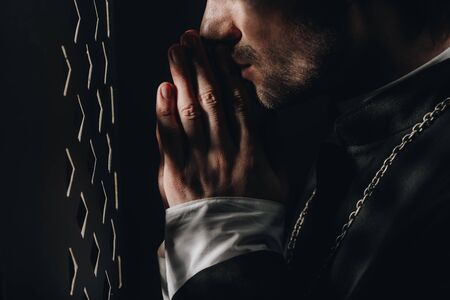 cropped view of catholic priest praying near confessional grille in dark with rays of light