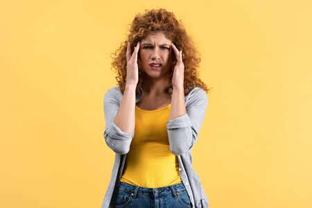 stressed redhead girl having headache isolated on yellow