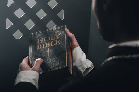 cropped view of catholic priest holding holy bible near confessional grille in dark with rays of light