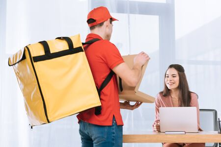Delivery man showing pizza in box at smiling businesswoman at table