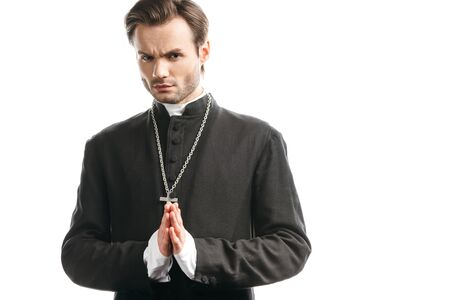 serious, strict catholic priest with praying hands looking at camera isolated on white