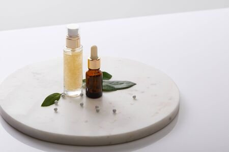 Bottles of cosmetic oil with leaves and decorative beads on round stand isolated on grey