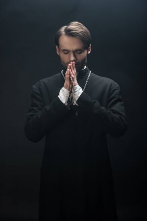 young concentrated catholic priest praying with closed eyes isolated on black