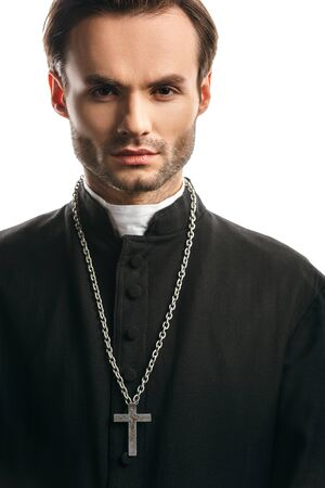 young, concentrated catholic priest with silver cross on necklace looking at camera isolated on white