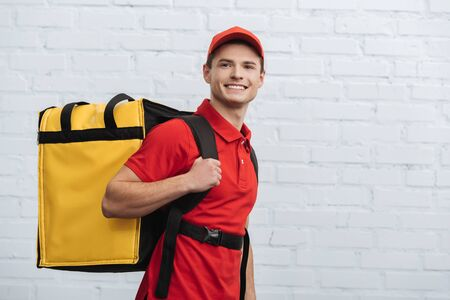 Smiling delivery man with thermo backpack looking away near brick wall