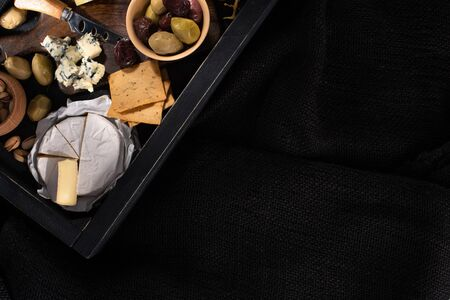 Top view of tray with pieces of camembert, dorblu, dried olives, crackers and pistachios isolated on black
