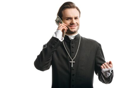 corrupt catholic priest looking at camera while holding money near head isolated on white