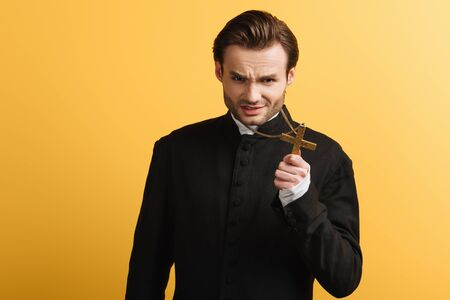 angry catholic priest showing holy christ while looking at camera isolated on yellow