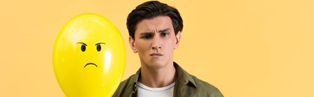 panoramic shot of skeptical man holding angry balloon, isolated on yellow