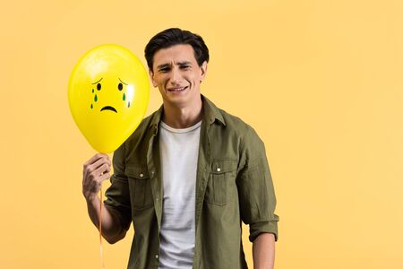 sad young man holding crying balloon with tears, isolated on yellow