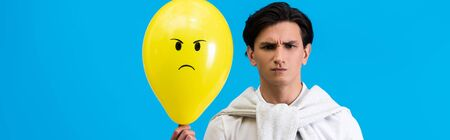 panoramic shot of aggressive young man holding yellow angry balloon, isolated on blue