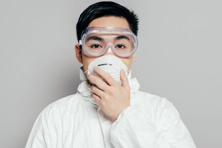 asian epidemiologist in hazmat suit touching respirator mask while looking at camera isolated on grey