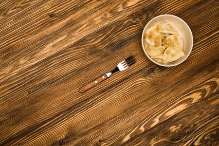 top view of delicious varenyky with fried onion in bowl on wooden table with fork