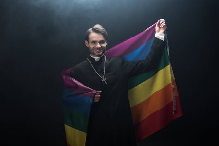 smiling catholic priest holding flag while looking at camera on black background with smoke