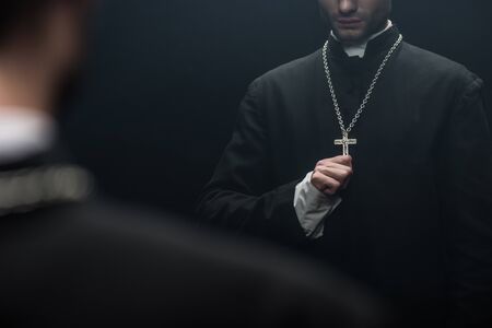 cropped view of catholic priest touching cross on his necklace near own reflection isolated on black