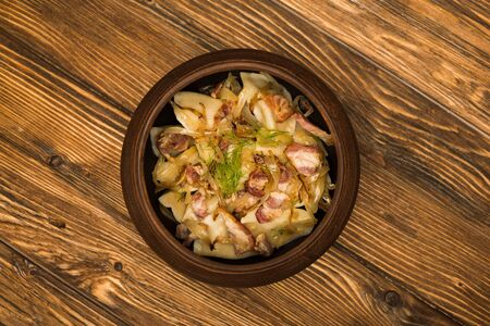 top view of delicious varenyky with cracklings in bowl on wooden table