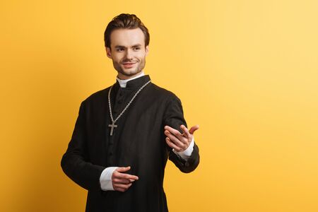 smiling catholic priest standing with outstretched hand while looking away isolated on yellow