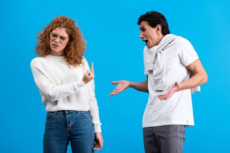 irritated girlfriend showing middle finger to angry boyfriend, isolated on blue