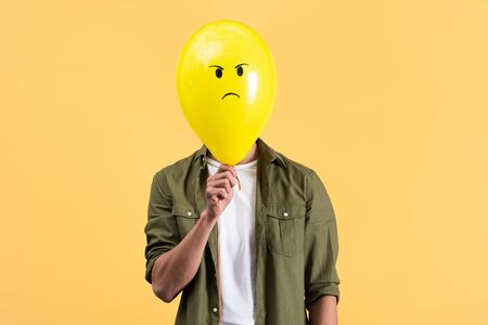 young man holding angry balloon in front of face, isolated on yellow