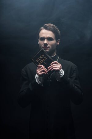 tense catholic priest looking at camera while holding holy bible on black background with smoke Stockfoto