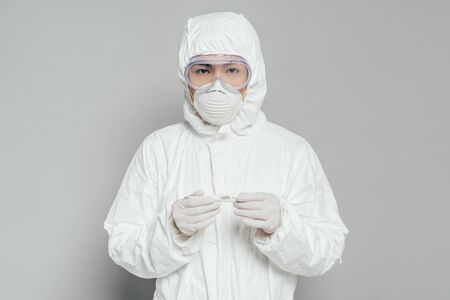 asian epidemiologist looking at camera while holding thermometer showing high temperature on grey background