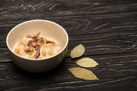 delicious varenyky with cracklings in bowl near bay leaves on black wooden table Stock fotó