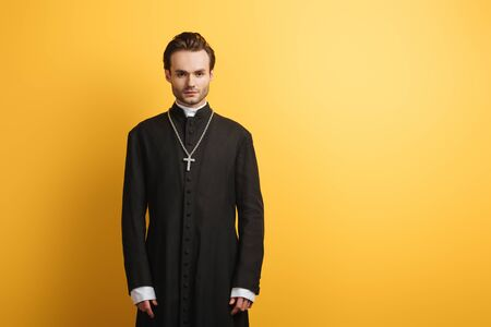 young, confident catholic priest looking at camera while standing isolated on yellow