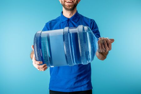 Cropped view of smiling courier holding bottled water isolated on blue Banco de Imagens