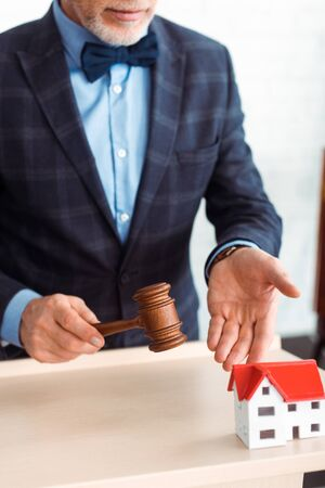 cropped view of auctioneer pointing with hand at model of house and holding gavel during auction Standard-Bild