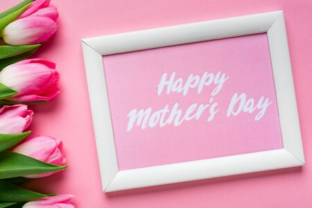 俯视图的框架与快乐的母亲节字母附近的郁金香在粉红色的背景