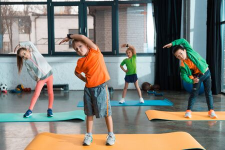 Selective focus of multicultural children warming up together on fitness mats in gym Imagens