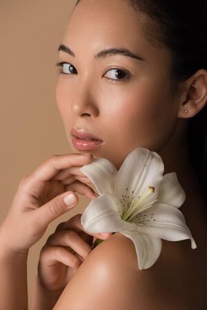 beautiful asian girl holding white lily isolated on beige
