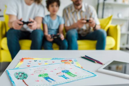 selective focus of papers with drawing near digital tablet and homosexual couple playing video game with mixed race son