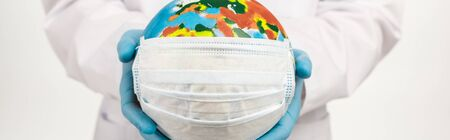 panoramic shot of scientist holding globe in protective mask isolated on white Stock Photo