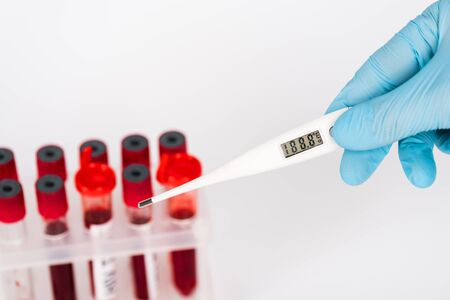 cropped view of scientist holding digital thermometer near test tubes isolated on white Stock Photo