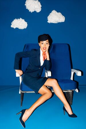shocked african american flight attendant sitting on seat on blue background with clouds