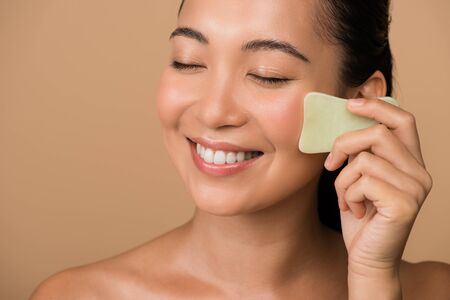 smiling beautiful asian girl with closed eyes using facial gua sha jade board isolated on beige