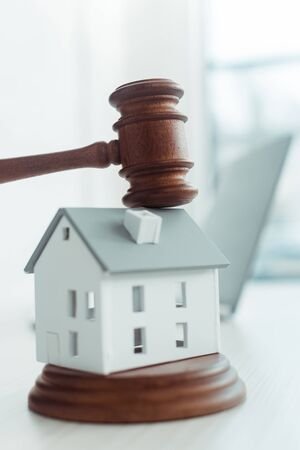 wooden gavel and model of house on table