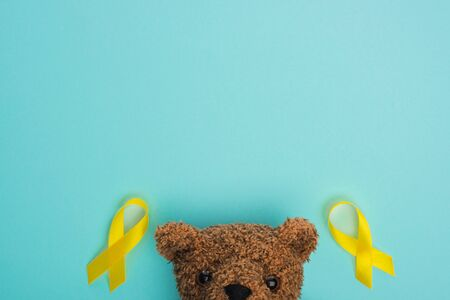 Top view of yellow awareness ribbons and brown teddy bear on blue background, international childhood cancer day concept