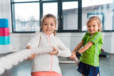 Selective focus of children smiling and playing tug of war in sports center